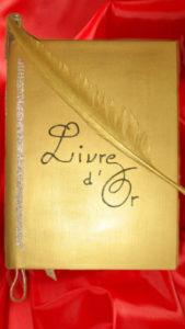 Livre d'or sur fond rouge avec une plume en or posée dessus
